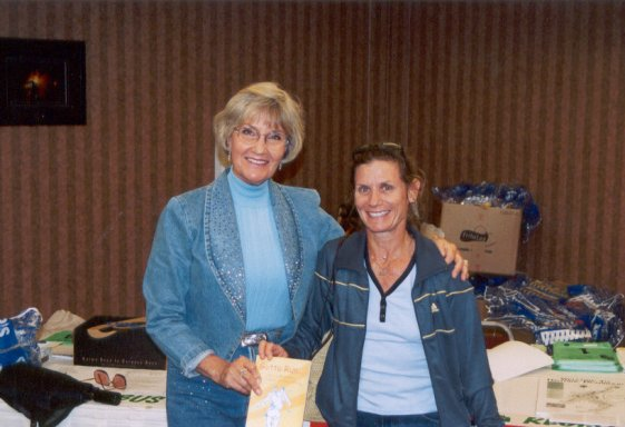 Elaine-Doll Dunn with Fillis Friedman at packet pick-up in Deadwood. Fillis getting an autographed copy of Elaine's book 'Gotta Run'.