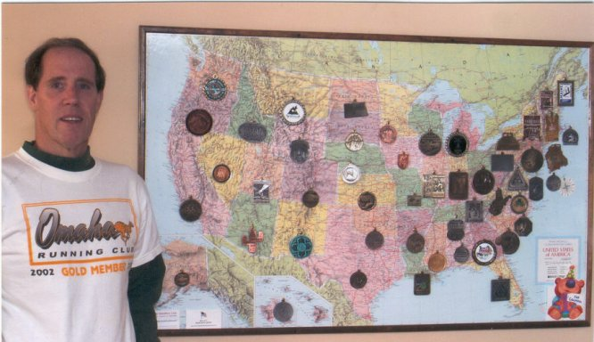 Mike Fleming stands in front of a map with his metals from all 50 states and DC in honor of his completion of the circuit!