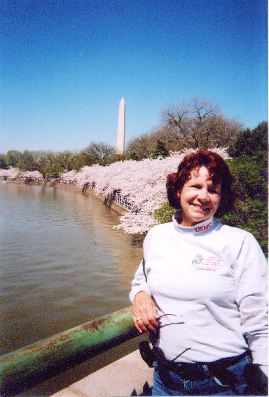 Donna Loud posing for a photo at the Marine Corps Marathon with the Washington Monument in the background.