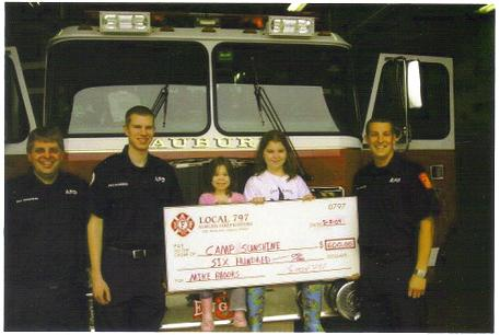 Auburn Firefighters' left to right Jon Woodhead,William Flanders , Mike's granddaughters McKenzie and Madison Brooks and Thomas Printup. Getting a check for Champ Sunshine for Mike?s goal of $10,000.