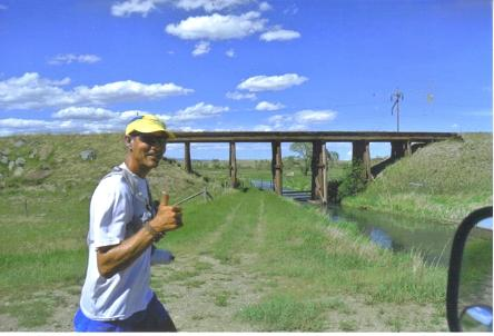 June 21,2012 Mike Samuelson a couple miles east of Martinsdale,MT on day 23 of the run across America on trail an old Milwaukee Road Railroad trestle is in the background.